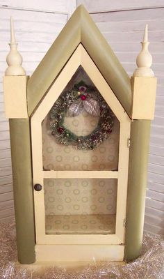 "Offered is an antique clock case with a glass-front door which has been turned into a display case. It is painted in soft green and cream and is lined in a holly themed pattern paper. On the back wall of case is an antique bottle brush wreath which is trimmed with miniature mercury glass beads. A beautiful way to display a favorite Santa of other Holiday piece! 20"" tall 10"" wide 3.5"" deep. $65.00 SALE $45."