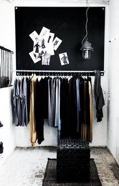 A built-in clothing rack is accented with a black pin board and accessories
