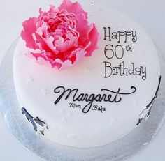 Round white 60th birthday cake with pink flower and cursive writing
