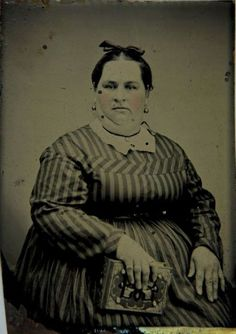 ca. 1856-1910, [hand tinted, tintype portrait of a woman in a fine striped dress, holding a book]