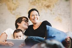 Stock Photo : Smiling lesbian couple and baby girl with digital tablet at home