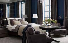 Chambre avec mur de miroirs, lit garni de nombreux textiles, fauteuil, lampadaires et fleurs coupées