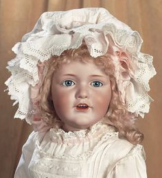 """German Bisque Child,241,by Kestner Known as Hilda Sister 25"""" (64 cm.) Bisque socket head,blue glass sleep eyes,dark eyeliner,painted lashes,short feathered brows,accented nostrils and eye corners,open mouth,shaded and accented lips,four porcelain teeth,impressed dimples at lip corners,blonde mohair wig,composition and wooden ball-jointed body. Condition: generally excellent. Marks: K made in Germany 14 JDK 241 (head) Germany (body). Comments: Kestner,circa 1915"""