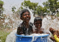 Boys sit in a plastic container filled with water as they cool themselves next to a borewell at a farmland on a hot summer day on the outskirts of Ahmedabad, India, May 28, 2015. A heat wave in India has killed at least 1,371 people this week as temperatures soar above 47 Celsius (116.6 Fahrenheit), and doctors' leave has been cancelled to help cope with the sick. REUTERS/Amit Dave