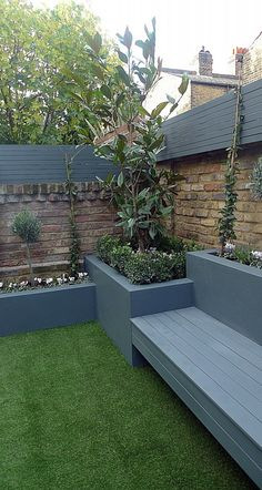 Grey colour scheme raised beds agapanthus olives artificial grass porcelain grey tiles grey Floating bench lighting Balham Clapham Wandsworth Battersea Fulham Chelsea London