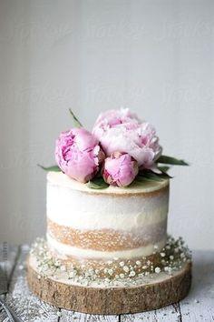 Naked wedding cake decorated with fresh flowers by Ruth Black for Stocksy United #WeddingCakeDecorating