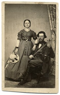 """Interesting hat, short sleeves & button (rosette?) trim that extends over the shoulder line towards the back.  The skirt appears to be more cone shaped than dome shaped   Carte de visite by Cook & Jones of Winona, Minn. The back of the mount of this photograph offers two clues as to the identity of this couple posed with a violin: The aforementioned photographer's name and location, and a pencil inscription, """"Mr. and Mrs. Porter June 20th 1864."""" Ronald S. Coddington collection"""