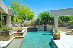 One of the many ways we mix the desert with modern features. From the glass tile to the running water feature. All elements here combine to form a very enjoyable outdoor living environment. #glasstile #travertine #palmtrees #landscape #design #cactus #pool #swimmingpool #spa #az #azluxury #luxury #houzz #design