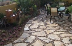 Inspiring outdoor patio designs. A patio of squares and rounds. Colored stones, surrounded by pavers of stained concrete, create the illusion of a stream bubbling. Best patio design ideas, for for back yard or front yard on your garden