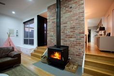 Cosy fireplace against old red brick feature wall