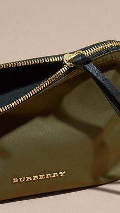 A durable pouch in canvas green with a zip-top gold closure and leather zip pull, from Burberry.