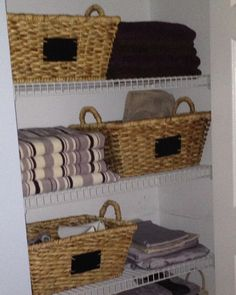 Linen closet organization - use baskets and open shelf to maximize space.
