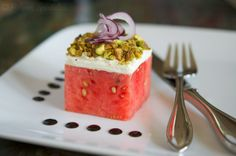 Stacked Watermelon Salad  Yield: Serves 4,         Ingredients:    Four 2x2x2-inch watermelon squares or circles  1/2 cup good quality goat cheese  1/2 cup roasted salted pistachios, chopped  1/8 cup shaved or thinly sliced red onion  1/4 cup balsamic vinegar