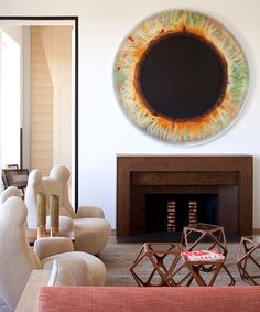 In Pierre Yovanovitch's Paris apartment, a large oil painting by Marc Quinn takes center stage above an acid-washed iron fireplace surround. The sofa and armchairs are Yovanovitch's own designs and the four cocktail tables are by Rasmus Fenhann.