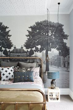A beautiful wall mural acting as a stunning backdrop to an antique brass headboard