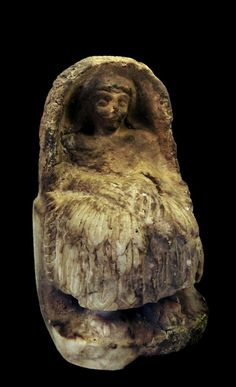 Sumerian alabaster statue of a worshiper wearing a calf-length woolen skirt with layers of tufted borders, the hands gathered together in an attitude of devotion, with cuneiform inscriptions on the back of the base. 2500 BC