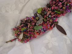 Rite of Spring is a hand knitted wire cuff bracelet made with 26-gauge fuchsia copper wire and silk cord in variegated colors knitted together.  There are two small copper-tone flower beads.  There is one tiny silver-tone metal butterfly charm.  There is one small silver-tone metal bumble bee b...