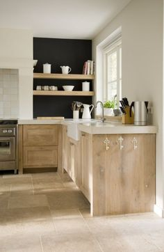 Beautiful Kitchen with great style cabinetry - love the natural wood on the cabinets, they go beautifully with the stone floors & open shelving .. Keukenblad en kastjes.