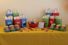 """Sesame Street Birthday Party favor table - Cookie Monster headbands, wands, noisemakers, kiddie gift bags made with Cricut cutouts and chocolate covered pretzel """"crayons"""" (original directions for crayons from http://www.partiesbyhardie.com/2009/07/pretzel-crayon-treats.html)"""