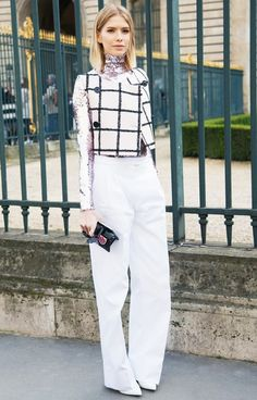 Elena Perminova wears a sequin turtleneck, graphic print cropped vest, high-waisted white trousers, pointed-toe pumps, and a Dior clutch
