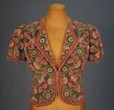 Elsa Schiaparelli Haute Couture beaded evening jacket from French 1930. Made from cropped sea green silk in short sleeve, collarless with lapel. Having an allover beaded embroidered meandering pattern of bell flowers and roundels in pink and blue beads with coral paillette sequin on a round of tiny bronze iridescent beads, edged in coral orbs, lined in changeable silk faille. Label Schiaparelli Paris. #Fashion #Hautecouture #Elsa #Schiaparelli