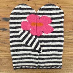 Inspired by pop art these mittens feature a bright flower against black and white stripes.