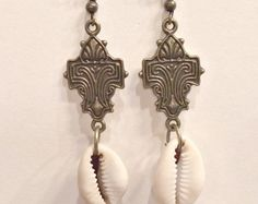 Tribal Style Earrings One of a Kind Mandala & Cowrie Shell  WHY COMMISSION INCENSE AND PEPPERMINTS? Our original one of a kind Tribal Style Earrings are skillfully hand tooled by Cherri. Every unique piece of jewelry is crafted with meditative reverence and resonates a powerful love vibration. Primitive Bronze ear-wires and findings enhance the ultra-high energy spiritual theme. Our focal point is a perfect Flower of Life Mandala, which we have enhanced with authentic drilled Cowrie Shell…