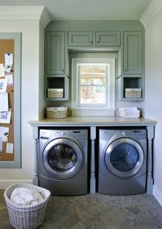 laundry/mud rooms - blue framed cork bulletin board silver front load washer dryer blue green built-in cabinets nook Large stone tiled laundry