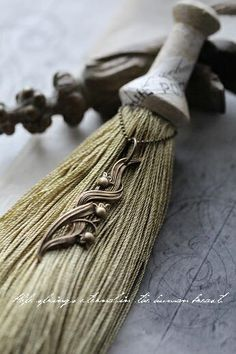 艶やかな輝きのある深みをました糸に古く加工したすずらんのパーツを。