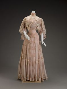 Dress, Girolamo Giuseffi, ca. 1906.  Silk and silk velvet. The appliquéd and cutout stylized flowers—either peonies or plum blossoms—are drawn in an Art Nouveau style. The dramatic sleeve silhouette along with the great amount of ruching and hand pin tucking throughout the bodice and skirt make this a very expensive garment, perhaps part of a trousseau.  Indianapolis Museum of Art.