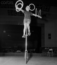 Ervine Hall (one of the Whiz Kids) riding unicycle while juggling hoops