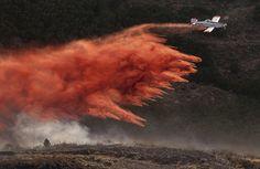 A plane dumps retardant on the fire in the foothills above Herriman on Friday, June 29, 2012. (Jeremy Harmon  |  The Salt Lake Tribune)