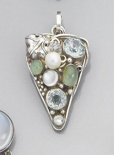 Possibly by Dorrie Nossiter. An Arts and Crafts gem set pendant. Unmarked,  the triangular mount of wires, beads and leaves, randomly set with two blue zircons, two moonstones, two green agate cabochons and a culture pearl, pendant 4.5 cm long. NB from www.dorrienossiter.co.uk: 'This is characteristically a piece of Dorrie's work even if not recognised as such by the auctioneers.' Sold by Bonhams, 22 May 2007, £504.00.