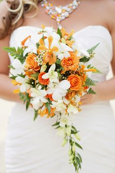 Gorgeous Petite Cascade Style Wedding Bouquet Arranged With: White Dendrobium Orchids + Buds, Orange Mokara Orchids, Orange Roses, White Wax Flower, Green Sword Fern & Additional Greenery/Foliage