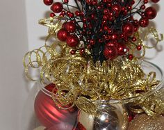 Want a beautiful and unique centerpiece for your christmas table? We offer unique, handmade christmas decor to compliment your personal christmas scheme. Looks great from all angles.  This centerpiece is a gorgeous combination of sparkling red and classic green ornaments topped with a beautiful assorted of colorful holiday ribbons and beads.  Approximate size 8x8x12  Back to our shop: http://glitterglassandsass.etsy.com  Want a custom color combination that exactly suits your decor? I am…