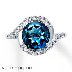 From SOFIA VERGARA, this breathtaking ring for her features a round blue topaz embraced by sweeps of sterling silver and round white topaz gemstones. Available online while supplies last.