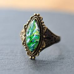 Green opal ring, featuring an unusual navette shape vintage glass opal, set in an ornate setting on top of an antiqued brass adjustable ring.