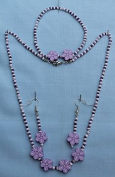 "Lilac and white acrylic flowers with white glass and purple seed beads.  Necklace: 46cm (18"").  Bracelet: 17.75cm (7"").  Earrings Drop: 2.7cm (1.1/8"").  Materials used: Glass, acrylic and silver coloured metal."