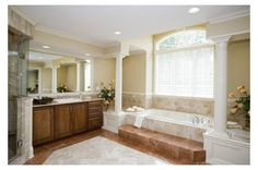 Opposite the sleek walk-in shower, graceful columns flank an arched window over the raised tub in this luxurious master bath from Heartland Homes near Pittsburgh