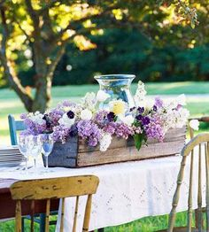 A wooden table topped with lilacs is the essence of country charm! More ideas: http://www.midwestliving.com/homes/outdoor-living/31-inspiring-outdoor-table-arrangements/