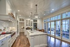 Kitchen in classical farmhouse with wall of French doors opening to screened porch. Architecture: Historical Concepts | Interior Design: Melanie Davis | Photo: Blayne Beacham
