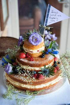 Homemade naked wedding cake with purple cake flag topper, flowers & fruits - Image by Fiona Kelly - Annasul Y Wedding Gown And No 1 By Jenny Packham Bridesmaids For A Rustic Wedding At The Thames Rowing Club With Groom In Kilt And A Touch Of Tartan Theme