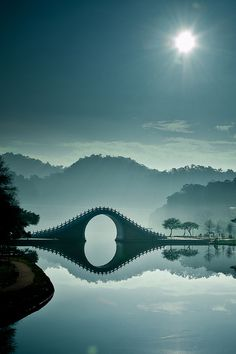 Stunning photo...The main focus of each marvelous image is the area around the Moon Bridge in Taipei, Taiwan. The soft blue, monochromatic palette and the sparkling rays of sunshine make the images feel so peaceful. The crystal clear water allows for a perfect reflection of an upside down world and his tones, lighting, and composition are exceptional.    via My Modern Metropolis.    new favourite, omg