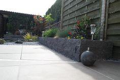 Verhoogde plantenbak van stapelstenen antraciet. Terrastegels 60x60cm onderhoudsvriendelijk