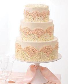 Wendy Kromer covered each tier of the cake in Swiss meringue buttercream, then created a repeated flourish with a petal tip, which gives the cake a modern style.