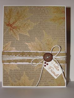 By Barb Engler. Stamp background text. Stamp leaves in VersaMark & heat emboss with gold powder. Use wild honey Distress stain to give them a bit of color. Add embellishments & sentiment.