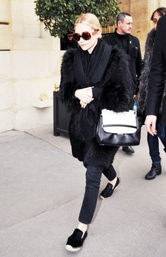 Ashley Olsen wears a black fur coat and black scarf with round sunglasses, skinny jeans, espadrilles and a black and white tote.