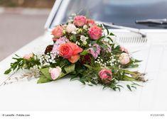 Kleines Autogesteck mit frischen Blumen für das Hochzeitsauto. Die Blumen-Dekoration ist mit einem Autoschmuck-Halter aus Steckschaum mit Saugnapf auf der Motorhaube befestigt.
