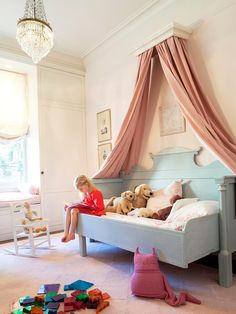 Sweet Canopy-Finish off a girl's fairy tale room with a sweet canopy and headboard. A scalloped headboard looks like a scene from a storybook and fills the majority of one wall. To complete the look, long curtain panels fall from a cornice hung near the ceiling and frame the bed.