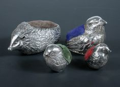 A matched graduated set of three silver pincushions modelled as chicks, the largest by Sampsom Mordan and Co, Chester 1905, 35mm high, the two smaller examples by Ari D Norman, London 1979 and 1985, each 25mm high, and a modern silver pincushion modelled as a hedgehog by A Ltd, Birmingham 1982, 6cm long (4)